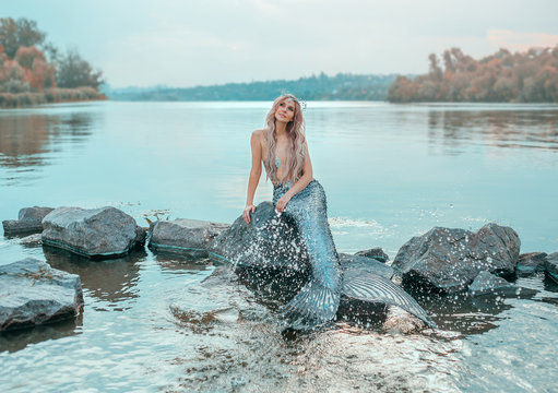 fair-haired mermaid in love dreams of handsome prince, new story Ariel, image of fairy-tale siren with long fish tail, chic crown of shells, plays, sprinkles clear water, ecology of environment