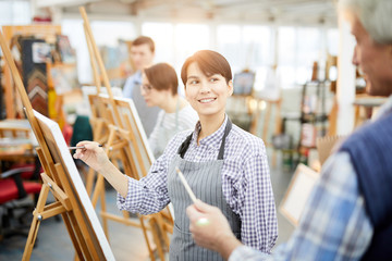 Waist up portrait of smiling young woman painting picture on easel in art class and looking at teacher, copy space