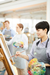 Side view portrait of young female artist holding palette and painting picture on easel enjoying work in art studio