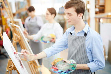 Side view portrait of smiling teenage boy holding palette and painting picture on easel enjoying work in art studio