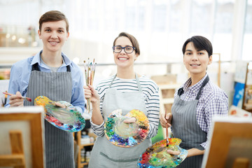 Waist up portrait of three cheerful art students looking at camera while posing in studio