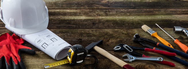 Building helmet and professional hardware tools on DIY wooden background