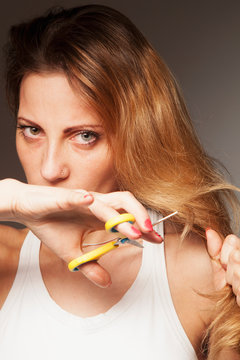 Upset woman cutting her her hair. Problem of split ends.