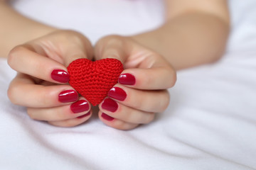 Declaration of love, red knitted heart in female hands on the white bed. Valentine heart, concept of romance, charity, save life or blood donation