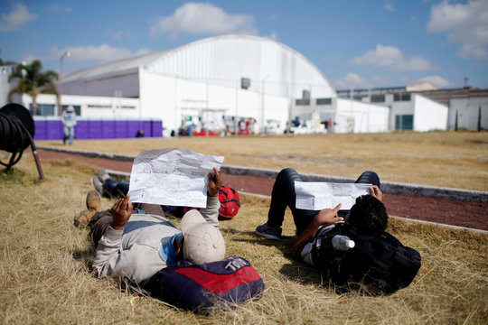 Migrants check maps of Mexico in a provisional shelter during their journey towards the United States, in Puebla, Mexico