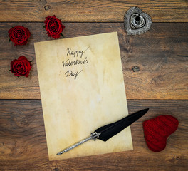 Vintage Valentine's Day card with 3 red roses, red cuddle heart, wooden decorations, detailed silver quill stand accented by beautifully ornamented silver and black quill - top view