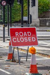 Verkehrsschild mit der Beschriftung Strasse Gesperrt in Englisch .Rotes Schild mit weissen Text zwei Verkehrskegel mit gelber Warnlampe