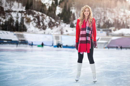 Woman ice skating outdoor at ice rink stadium.