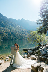 Beautiful wedding couple standing on the stony shore of the lake Morski oko in the mountains.