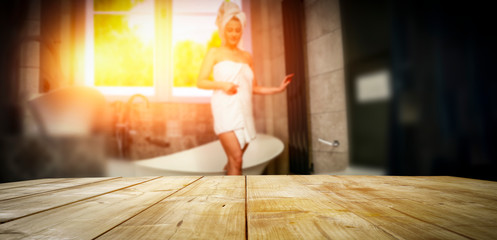 A wooden table and a girl in the bathroom with a beautiful sunset coming through the window