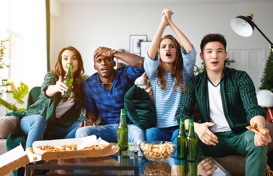 group of happy friends fans watching a match on tv with beer and pizza at home