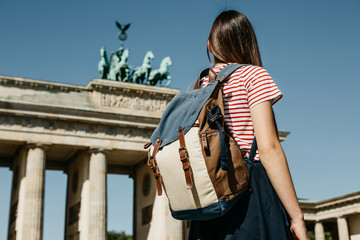A tourist or a student with a backpack near the Brandenburg Gate in Berlin in Germany, looks at the...