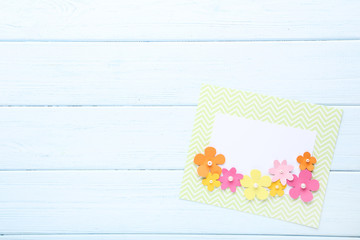 Handmade greeting card with paper flowers on wooden table