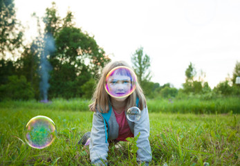 Cute preschooler girl playing with soap bubbles