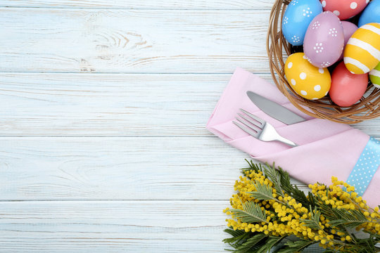 Kitchen cutlery with easter eggs and mimosa flowers on wooden table
