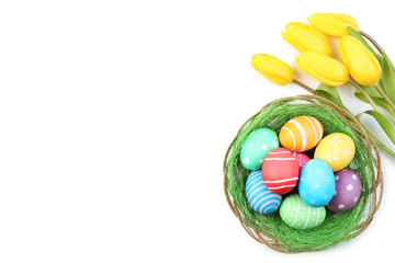 Colorful easter eggs with yellow tulips on white background
