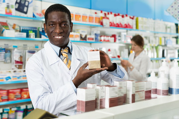 Portrait of experienced male pharmacist counseling about medicines in pharmacy
