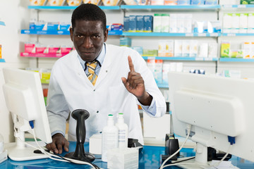 male pharmacist drawing attention of clients