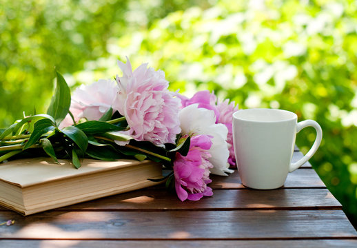 book, flowers and a cup of tea on a table in a spring garden, spring or summer card or calendar
