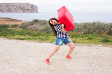 People, travel and holidays concept - young woman is trying to lift her luggage up
