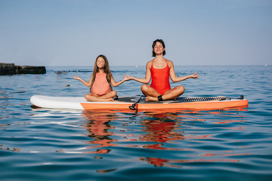 Mom and little daughter doing yoga on the paddle board