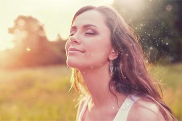 Fototapeta Young woman on field under sunset light