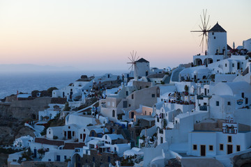 View of Oia Village with windmills at sunset, Santorini Greece