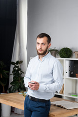 Theme office business. Handsome young caucasian man confident and strong with beard standing in bright room on working place. dressed stylishly shirt and trousers. Uses technology. Hand mobile phone
