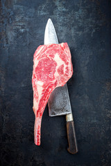 Traditional raw dry aged wagyu tomahawk steak as closeup on an old rustic board with large knife with copy space