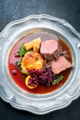Traditional saddle of venison with fried mashed potatoes and red cabbage in game red wine sauce as top view on a pewter plate