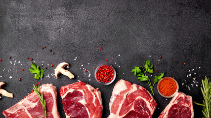 Meat raw steaks lie on a black background with vegetables, tomatoes, marasmade, mushrooms. background image. side view, copy space, top view Wall mural
