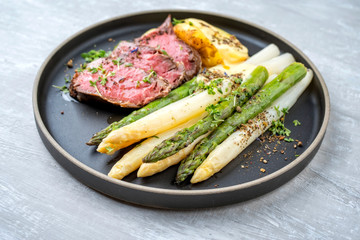 Traditional white and green asparagus with barbecue dry aged sliced beef fillet and fried potatoes served as closeup on a modern design plate