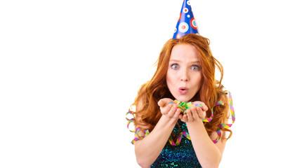 mädchen mit partyhut und roten haaren pustet konfetti
