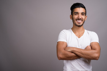 Young handsome Persian man against gray background