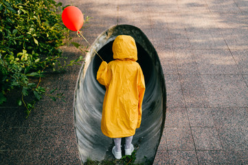 Portrait of pretty litle girl in big adult oversized yellow raincoat with red balloon in hand standing and sitting against sewage tunnel pipe. Scary movie concept. Funny child posing in summer day.