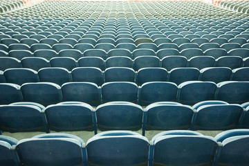 A row of empty green seats in a football stadium