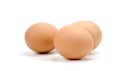 three chicken eggs on a white background