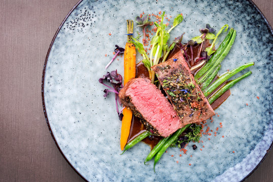 Traditional barbecue aged venison backstrap roast with green asparagus, carrots and herbs in brown red wine sauce as top view on a modern design plate with copy space
