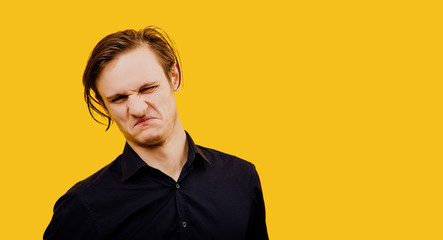 loathing young man,negative human emotion facial expression, yellow background, isolated