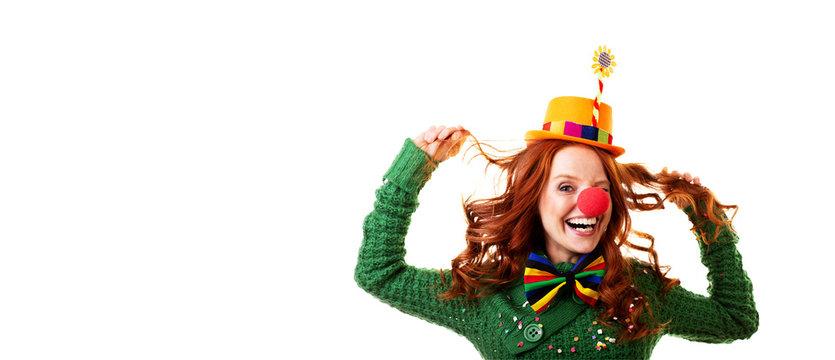 Frau mit roten haaren und blauen augen als clown verkleidet mit roter nase