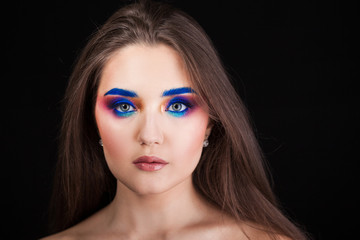 Attractive brunette with bright stylish make-up. Colored Smokey eyes and blue eyebrows.