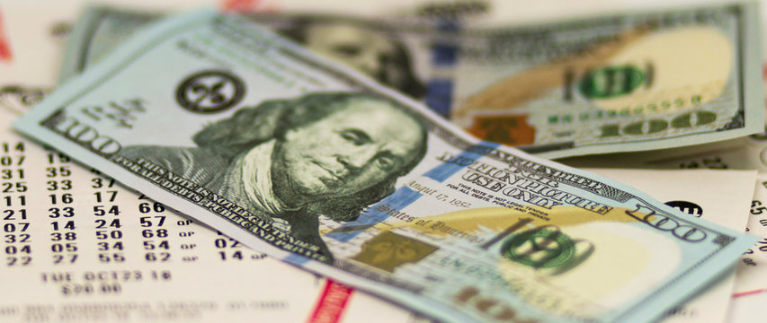 One hundred dollar bills over lottery tickets