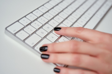 Closeup of female hands typing on white keyboard who is working at office and using computer