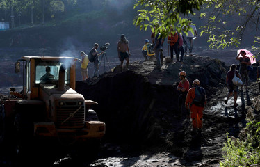 Members of a rescue team search for victims after a tailings dam owned by Brazilian mining company Vale SA collapsed, in Brumadinho