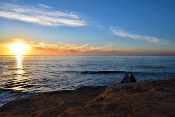 Couple sitting on a cliff at sunset