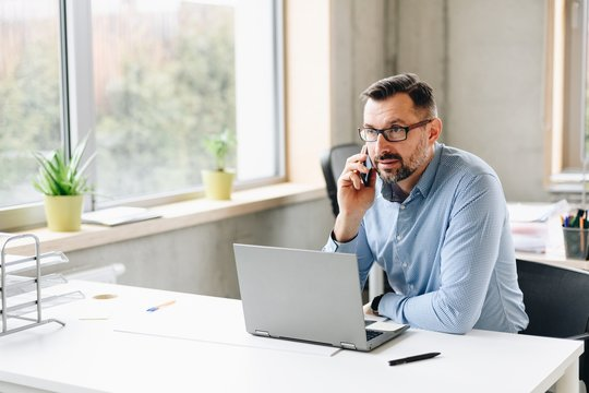 Middle aged handsome businessman in shirt working on laptop computer in office