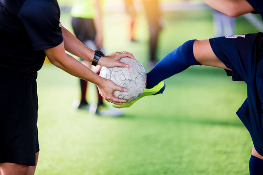 young boy soccer player kick ball in hands of coach