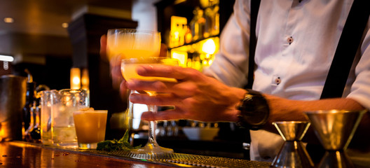 Bartender with cocktails at a busy bar with motion blur. Bartender handing drinks to server with movement blur.