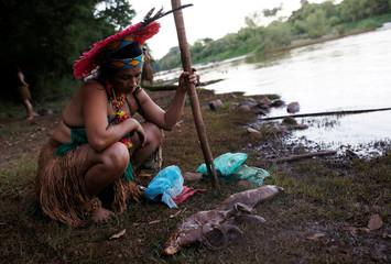 An Indigenous woman looks at dead fish near Paraopeba river in Sao Joaquim de Bicas