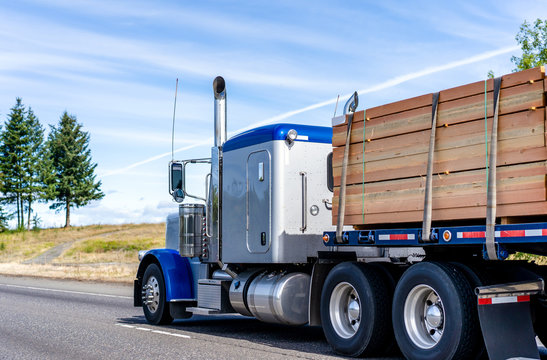 Big rig classic blue bonnet semi truck tractor transporting lumber wood on flat bed semi trailer on the road with hill on the side